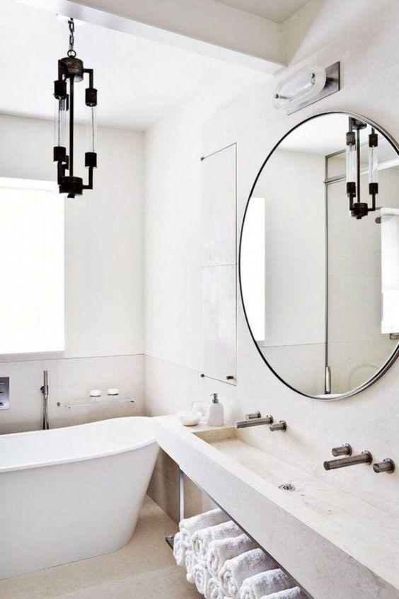 un accogliente bagno scandinavo neutro con molta pietra e cemento, una vasca e un lampadario accattivante