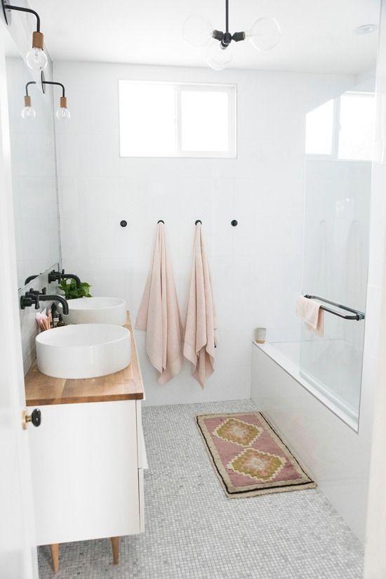 un piccolo bagno scandinavo con asciugamani arrossati, un tappeto rosa, un lavabo con piano in legno e lavandini