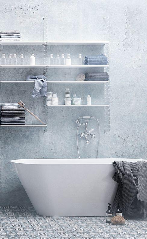 un bagno bianco sporco e grigio con piastrelle a mosaico sul pavimento, una vasca e un grande scaffale aperto
