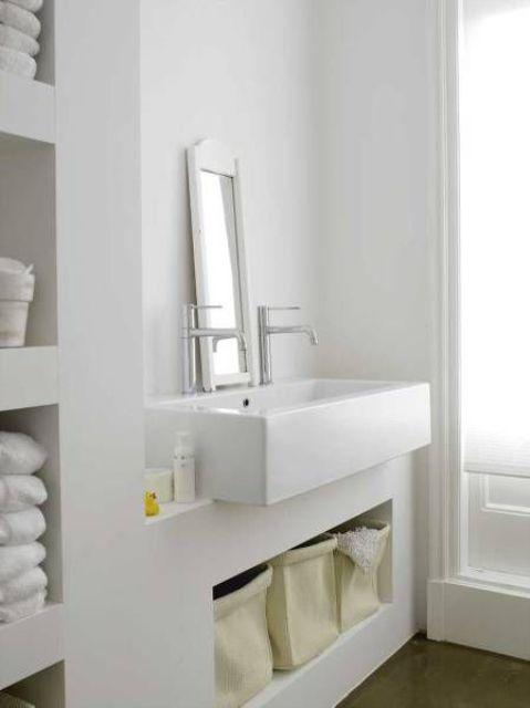 un bagno bianco minimalista fatto con cemento bianco dappertutto, un grande lavandino e molto spazio per riporre sembra veramente nordico