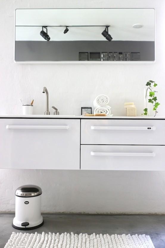un bagno nordico casual con una vanità bianca, un grande specchio, un tappeto bianco e un bidone della spazzatura