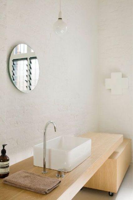 un bagno scandinavo neutro con piastrelle bianche, un lavabo in legno chiaro e una lampadina a sospensione
