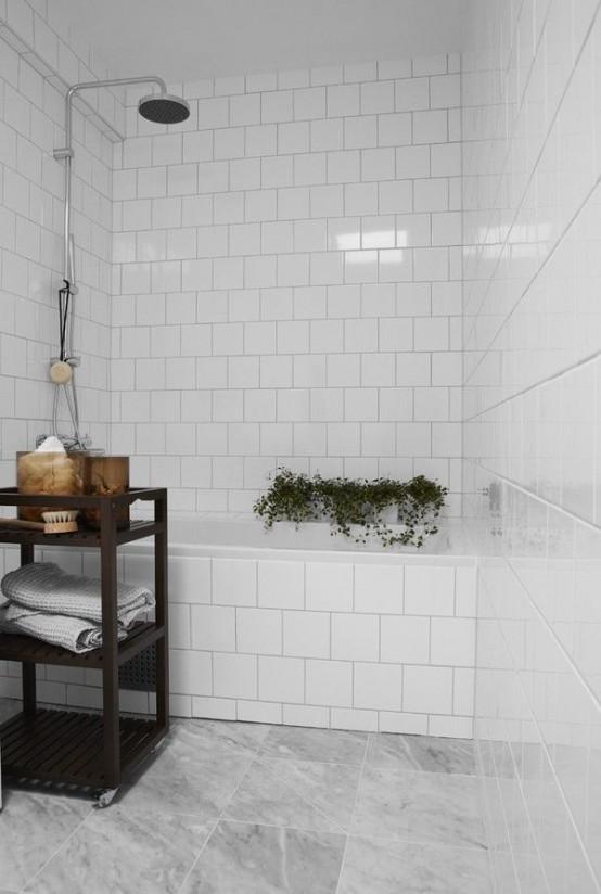 un piccolo bagno con piastrelle in marmo bianco e grigio, un mobile contenitore macchiato scuro e alcune piante in vaso