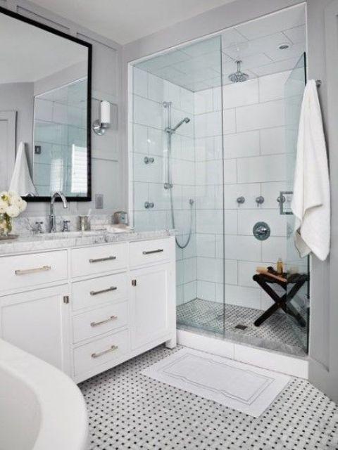 un sereno bagno bianco con un pavimento di piastrelle a mosaico, una vanità con un piano di lavoro neutro e uno spazio doccia vetrato
