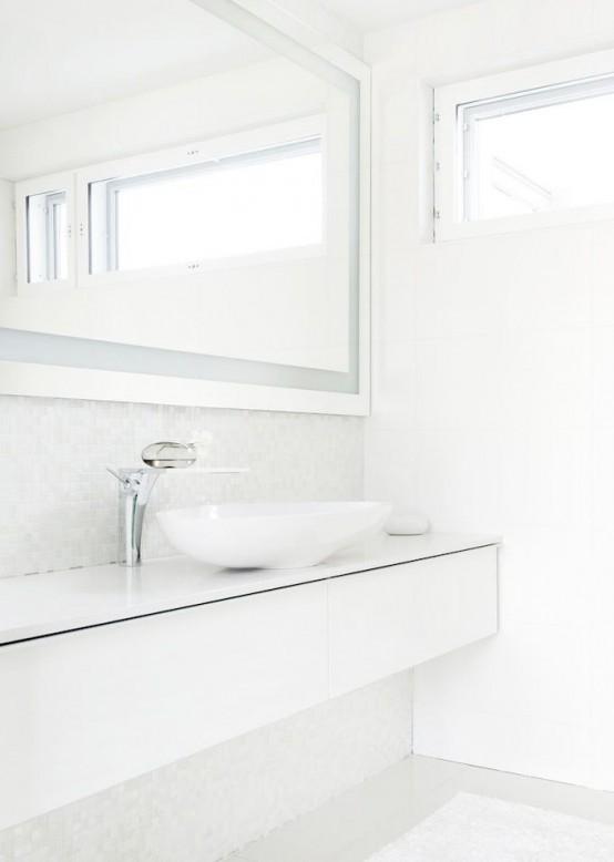 un bagno nordico fresco con una vanità lunga ed elegante, un grande specchio e un lavandino