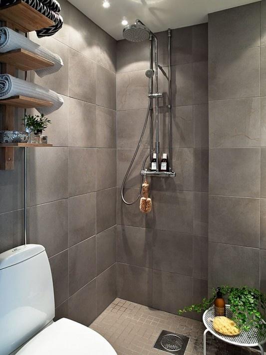 un bagno scandinavo grigio con uno scaffale aperto, piante in vaso e un piccolo spazio doccia