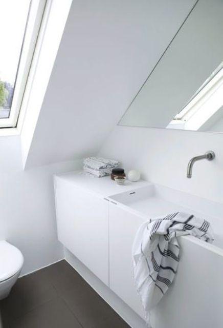 un piccolo bagno mansardato nordico con lucernario, lavabo integrato e specchio triangolare