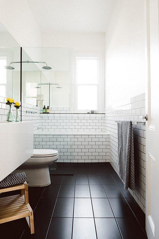 un bagno scandinavo in bianco e nero, con legno naturale e asciugamani stampati