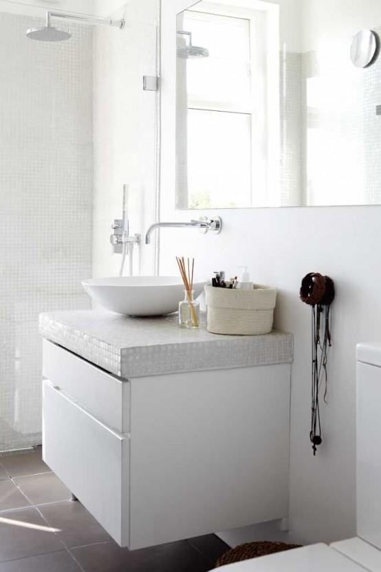 un laconico bagno nordico con mini piastrelle bianche alle pareti e vanità, un lavandino e un grande specchio