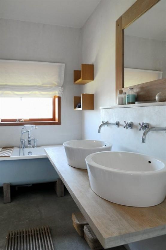 un rilassante bagno scandinavo con una vasca vintage blu, grandi lavandini e un grande specchio