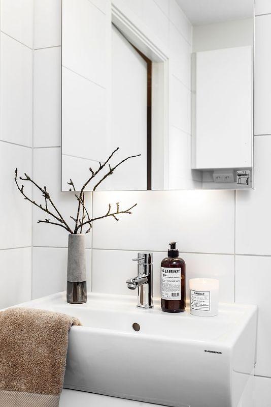 un bagno nordico con piastrelle bianche, un lavandino bianco, un grande specchio e una disposizione dei rami