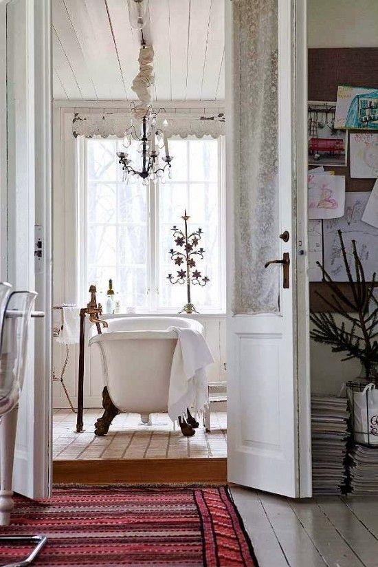 un bagno scandinavo shabby chic con un lampadario sopra la vasca e accessori vintage