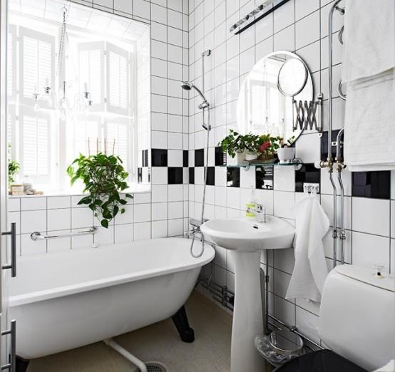 un bagno nordico con un tocco retrò realizzato in bianco e nero, con piante in vaso per un tocco di freschezza e una vasca da bagno vintage