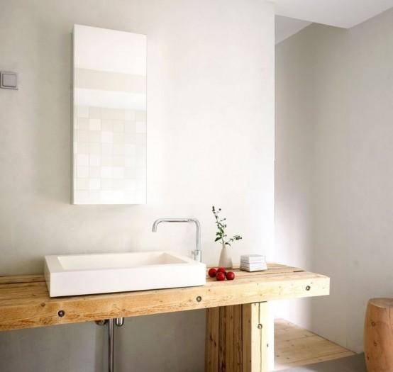 un lavabo in legno chiaro, uno specchio rettangolare, uno sgabello e un vano doccia con pavimento in legno