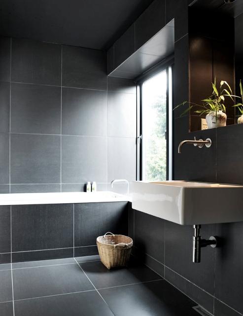 un lunatico bagno nordico completamente rivestito con grandi piastrelle grigie, con un lavandino a parete e una vasca rivestita di piastrelle