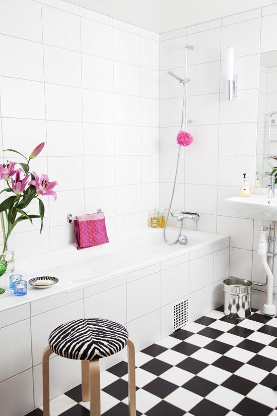 un bagno nordico in bianco e nero decorato con tocchi e stampe rosa acceso