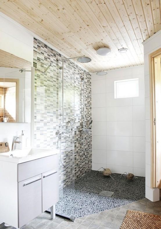 un bagno nordico neutro con un soffitto in legno, un muro di piastrelle a mosaico e un pavimento di ciottoli e una vanità bianco sporco