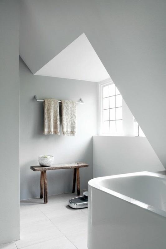 un piccolo bagno nordico mansardato con una piccola vasca, una panca, asciugamani stampati e molta luce naturale