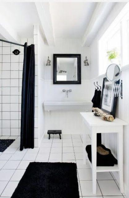 un semplice bagno nordico in bianco e nero con tessuti neri, piastrelle bianche con stucco nero e mobili bianchi