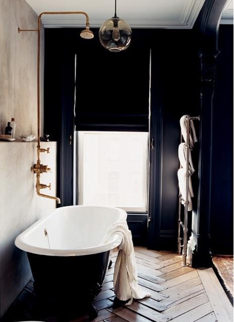 un bagno in stile art déco della marina con vasca vintage, rubinetti in ottone e sfumature romane