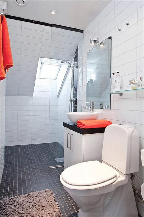 un moderno bagno nordico in bianco e nero con asciugamani rossi e un lucernario per la luce naturale nella doccia