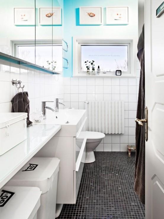 un bagno Scandi in bianco e nero con un tocco di opere d'arte ispirate al mare e al blu