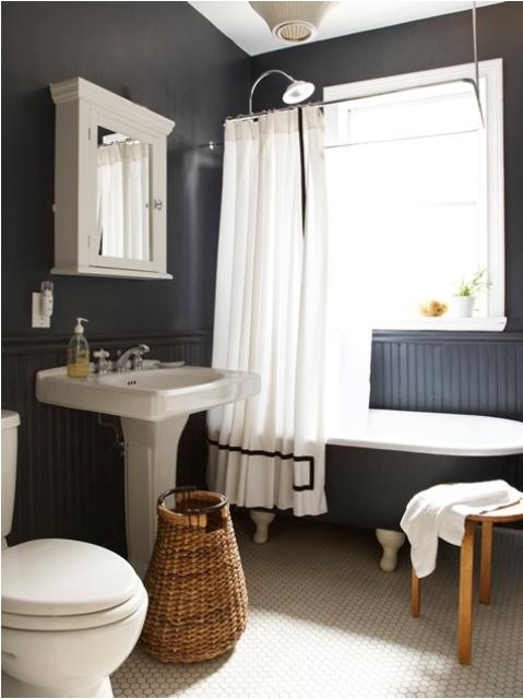un bagno scandinavo in bianco e nero con una vasca vintage, uno sgabello, un cestino e uno specchio vintage