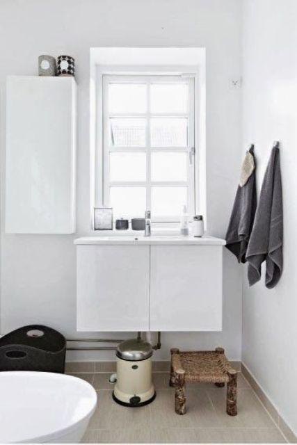 un piccolo bagno nordico bianco con uno sgabello in vimini, una vasca, un lavabo e un mobile contenitore chiuso