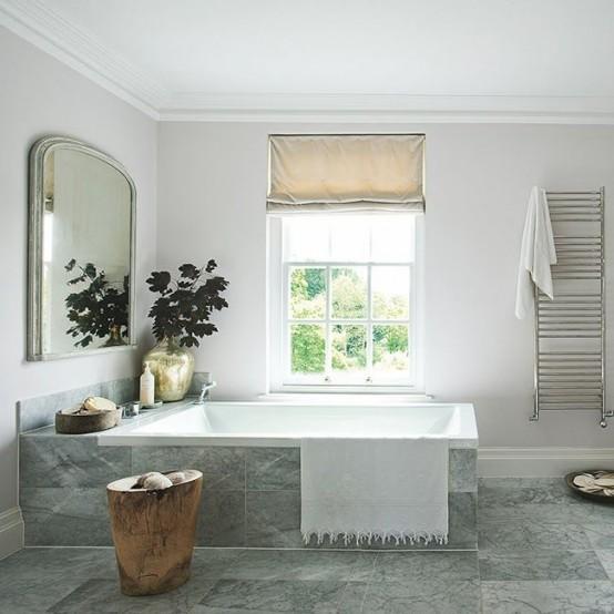 un bagno scandinavo grigio e bianco sporco con sfumature romane, un grande specchio e un tavolo di tronchi d'albero