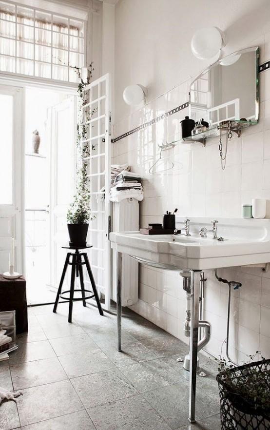 un bagno nordico vintage realizzato in una combinazione di colori neutri, uno sgabello vintage, un lavandino e uno specchio con una mensola