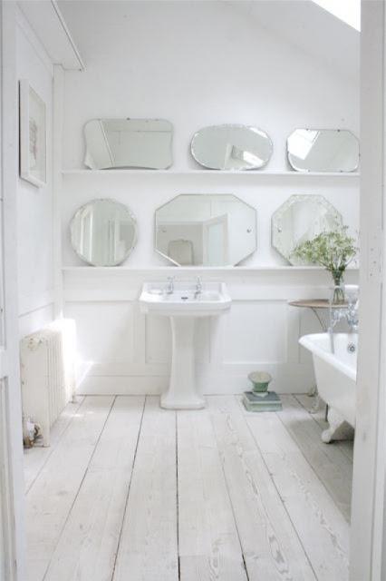 un bagno nordico chiaro e sereno con un pavimento in legno imbiancato, molti specchi in mostra e una vasca vintage