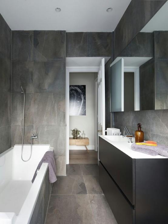 un bagno minimalista con piastrelle in marmo grigio dappertutto, una vanità grigio grafite e un grande specchio
