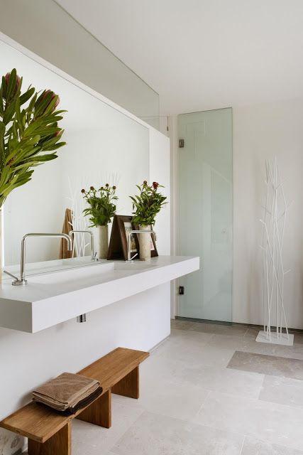 un bagno scandinavo contemporaneo fatto in neutri, con piante in vaso e una panca in legno