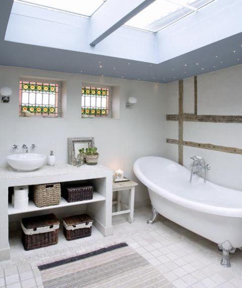 un bagno nordico neutro con lucernari, un lavabo con contenitori e una vasca vintage