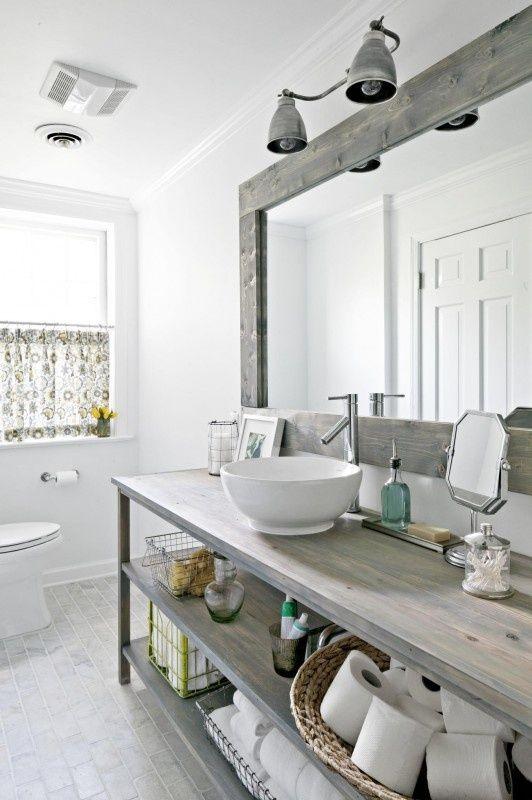 un bagno nordico vintage con un lavabo in legno, un grande specchio incorniciato e una tenda stampata sulla finestra