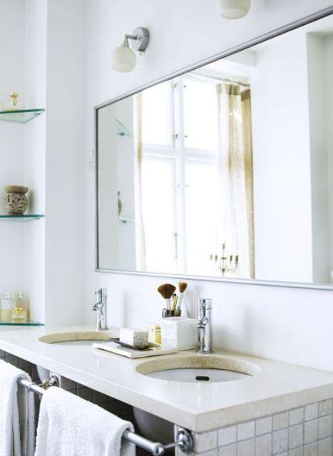 un semplice bagno scandinavo con ripiani in vetro, un piano di lavoro in pietra e piastrelle bianche