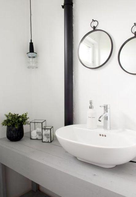 un fresco bagno nordico con un lavabo in legno imbiancato, specchi rotondi e una lampadina