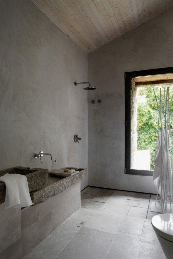 un bagno nordico minimalista fatto con piastrelle di cemento e pietra, lavandini in pietra e una grande finestra