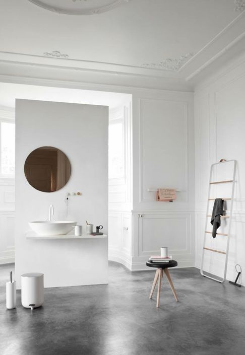 un bagno scandinavo con un lavabo sospeso, uno specchio in rame e alcuni mobili moderni