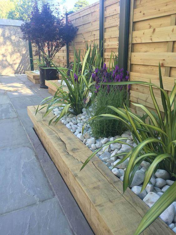 un bordo da giardino in legno, fiori luminosi e vegetazione, il tutto ricoperto da ciottoli neutri sulla parte superiore