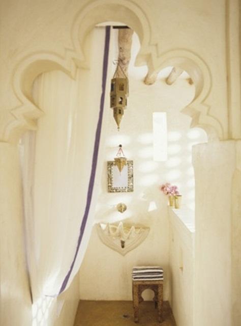 un bagno neutro con una porta intagliata, uno specchio decorato, un lavandino a conchiglia, una lanterna marocchina e una tenda