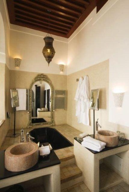 un bagno neutro con lanterne marocchine, lavandini in pietra, una vasca da bagno incassata, uno specchio decorato