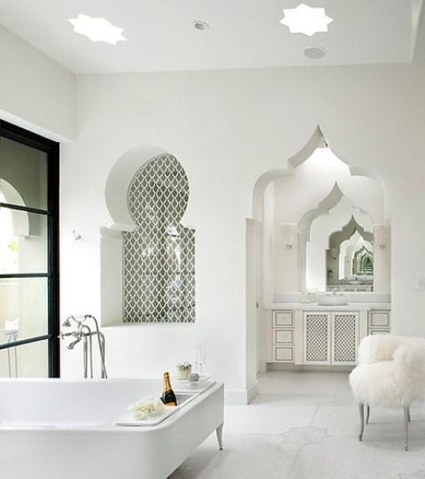 un bagno bianco puro con una porta intagliata, una nicchia piastrellata ad arco, una vanità intagliata e una sedia moderna