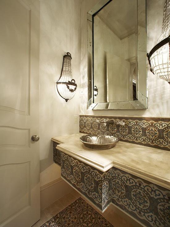 un bagno neutro con piastrelle a motivi geometrici che rivestono la vanità e il muro, con lampade da parete accattivanti