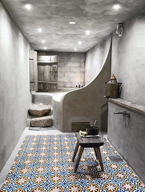 un bagno marocchino contemporaneo in cemento e con piastrelle a motivi geometrici sulle pareti e sul pavimento, con un semplice sgabello e gradini in legno
