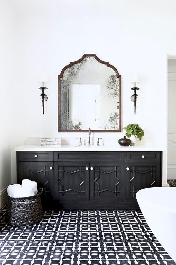 un bagno marocchino monocromatico con un lavabo in legno intagliato, un pavimento piastrellato e uno specchio dalla forma accattivante