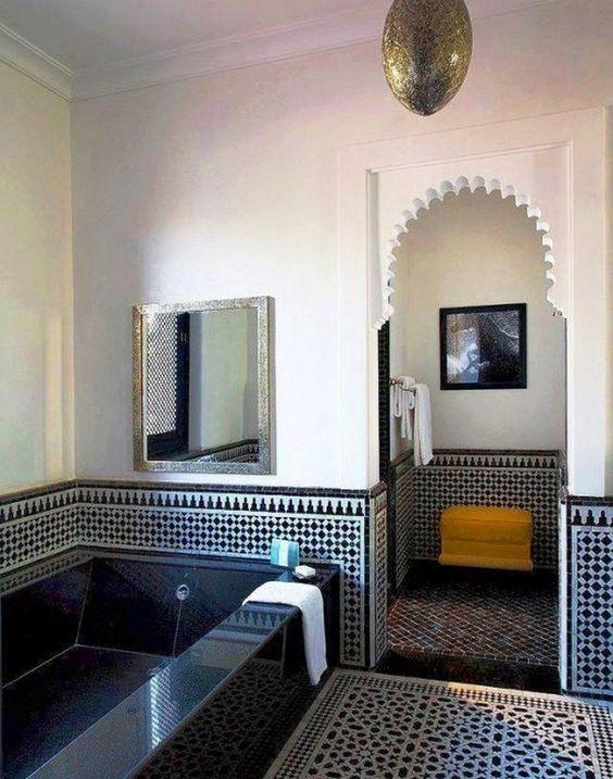 un bagno blu scuro e bianco con pareti e pavimento in gesso e piastrelle, una vasca da bagno piastrellata e una lampada a sospensione