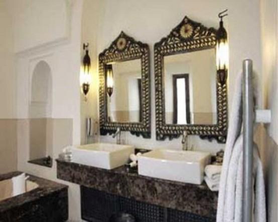 un bagno marocchino monocromatico con un lavabo in pietra, specchi decorati e lampade da parete