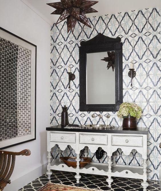 un bagno marocchino monocromatico con piastrelle accattivanti sul muro e sul pavimento e una vanità intagliata