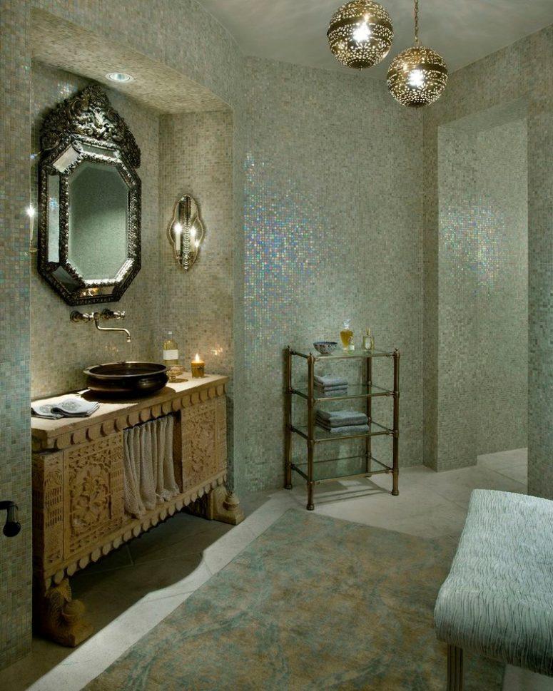 un bagno in madreperla con un lavabo in legno intagliato, uno specchio decorato e alcune lampade a sospensione (Nance Construction)